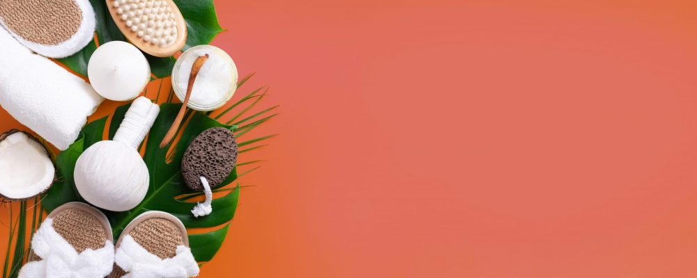 Spa, wellness, skin care, beauty and relax concept. Spa tools: white towel, bamboo slippers, herbal ball, cream, wooden brush, coconut oil, monstera on yellow background